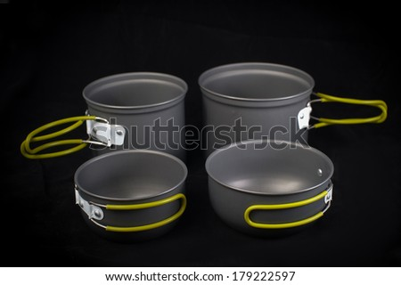 Set of tourist camping tableware with folding handles, isolated on black background - stock photo