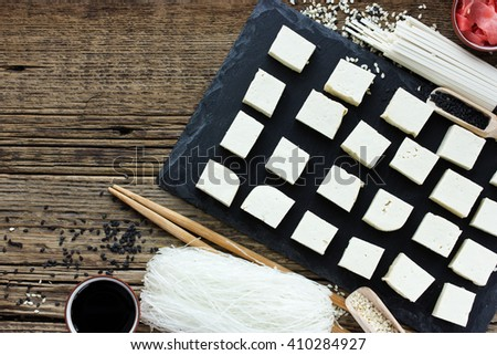 Set of traditional japanese food on wooden background. Asian food background. Ingredients of traditional cuisine: tofu, soy sauce, sesame paste udon rice noodles, pickled ginger blank place for text - stock photo