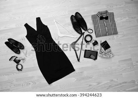 Set of trendy clothes. Outfit of man and woman clothes and accessories on light wooden background - stock photo