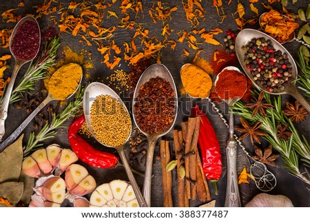 Set of various aromatic colorful spices in old vintage spoons and herbs on a dark wooden background. Ingredients for cooking. Top view - stock photo