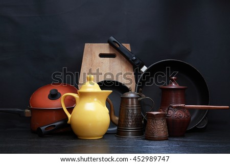 Set of various kitchen dishes on dark background - stock photo