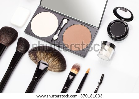 Set of various makeup brushes with eyeshadow and rouge or powder. Overhead view of cosmetics stuff - stock photo