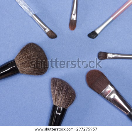 Set of various natural bristle make-up brushes: for applying blush, powder, foundation, cream and compact eyeshadow on blue background - stock photo