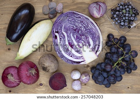 Set of vegetables and berries on aged wooden background: onion, eggplant, cabbage, beetroot, garlic, grape, black currant.  - stock photo