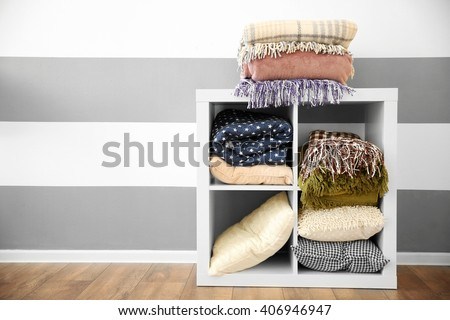 Set of warm plaids and pillows on white shelf against striped wall background - stock photo
