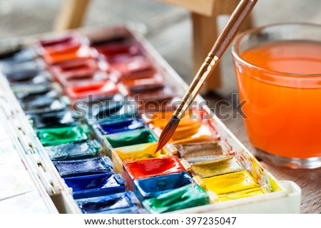 Set of watercolor paints and paintbrushes for painting closeup. Selective focus.  - stock photo