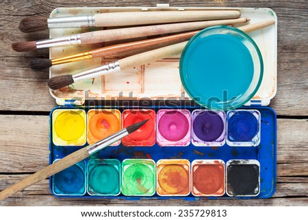 Set of watercolor paints, art brushes and glass of water on old wooden table. Top view. - stock photo
