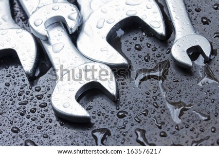 Set of wet spanners  on black metal - stock photo