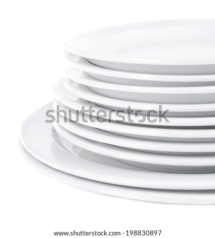 Set of white dishes on table on light background - stock photo