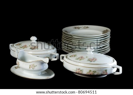 set of white dishware isolated on black background - stock photo