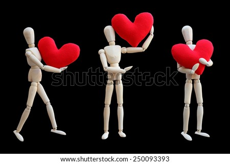 Set of Wooden dummy holds red heart for love isolated on black - stock photo