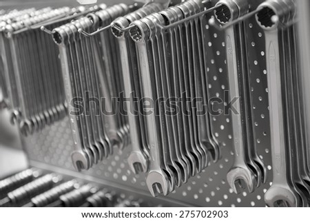 Set of wrenches hanging on grey wall background - stock photo
