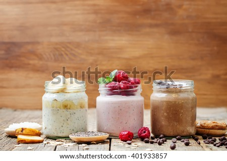 set overnight oats with berries, coconut, peanut butter, Chia seeds and chocolate chips. toning. selective focus - stock photo