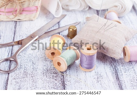 Set reel of thread, scissors, needle and thimble for sewing and needlework in the style Shabby Chic - stock photo