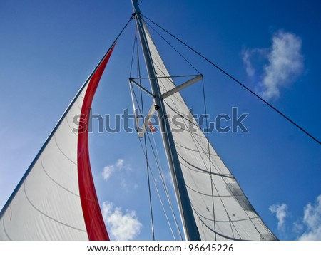 Set sails against a beautiful blue sky - stock photo