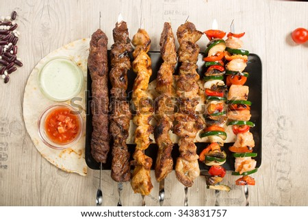 set shashlik. kebab skewer, black rectangular plate. sauce and onions - stock photo