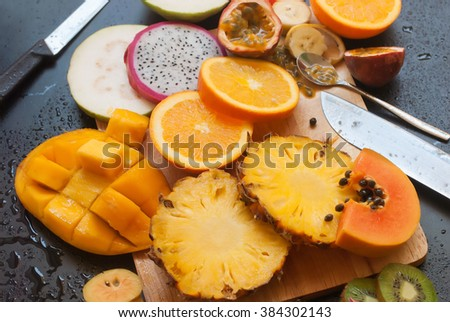 Set Tropical Cut Fruits  Banana Papaya Pine Apple Kiwi Mango Passion Fruit Sapodilla Dragon Orange Black Wooden Background Top View - stock photo