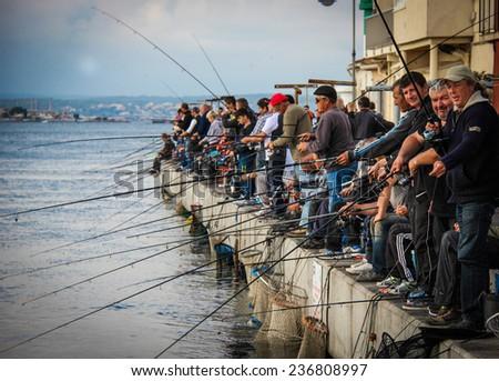 SETE, FRANCE - NOVEMBER 2: Men fishing off the pier on November 2, 2014 in Sete, France - stock photo