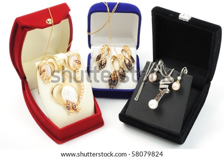 Sets of gold jewelry in open boxes, on white - stock photo