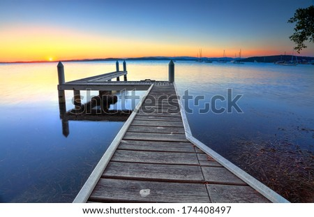Setting sun on the horizon at Belmont, view from the jetty. - stock photo
