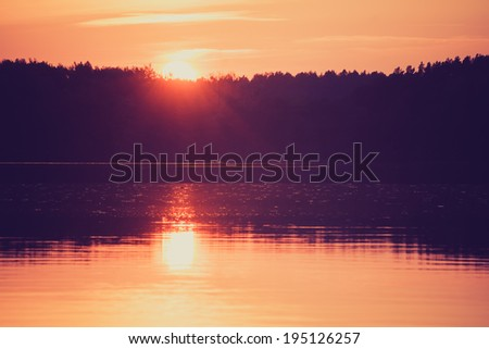 Setting sun over a lake . Silhouetted trees are seen against the sky. Processed and toned for a vintage faded retro look. - stock photo