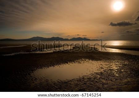 Setting sun shot from Newborough beach, Anglesey, Wales, - stock photo