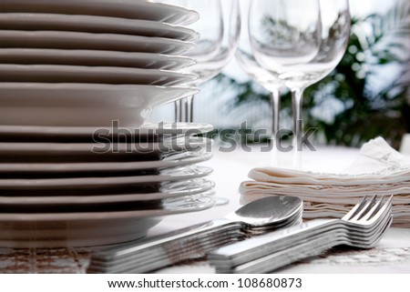 Setting the table with wine glasses, dishes, napkins, forks and spoons over a embroidered linen tablecloth. Window at the background. - stock photo