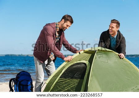 Setting up a tent. Two cheerful young men setting up a tent while standing at the riverbank  - stock photo