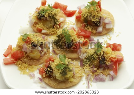Sev Puri Fried flour (puri) topped with sev, onion,potato and other masala - stock photo