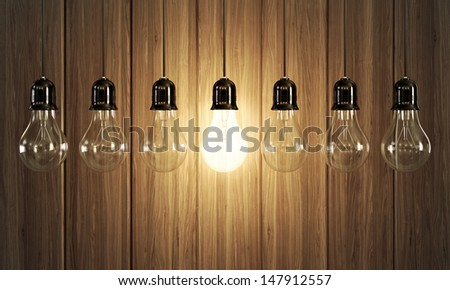 Seven light bulbs with glowing one on wooden background. - stock photo