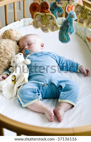 Seven month old baby boy sound asleep in his crib - stock photo