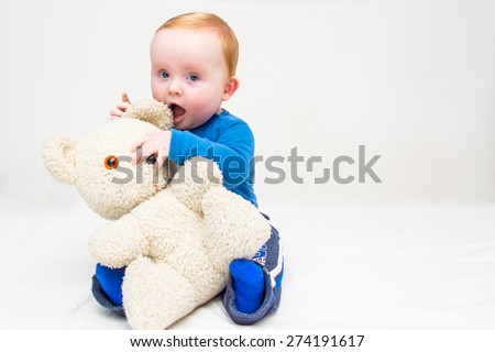 Seven month old white baby boy, with blue eyes and red hair, sitting on a white mattress and plays with his teddy bear. He is wearing a blue bodysuit and blue socks. Isolated on white. - stock photo