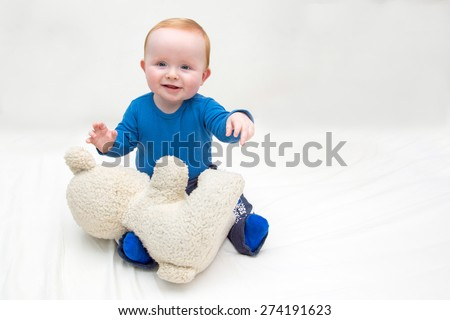 Seven month old white cheer full baby boy, with blue eyes and red hair, sitting on a white mattress and plays with his teddy bear. He is wearing a blue bodysuit and blue socks. Isolated on white.  - stock photo