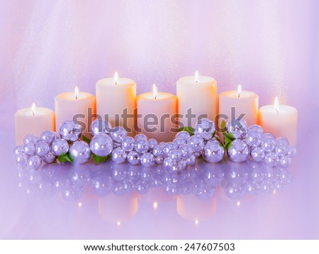 Seven pillar candles lit make up a centerpiece with silver grape cluster bulbs. All are reflected in a glassy surface and glow with a romantic purple mood. - stock photo