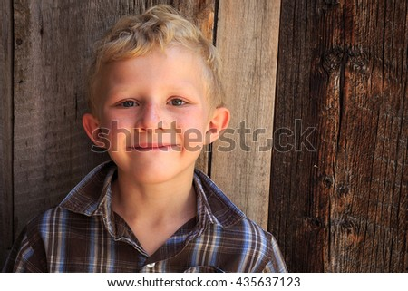 Seven year old boy with a natural barn wood background. - stock photo