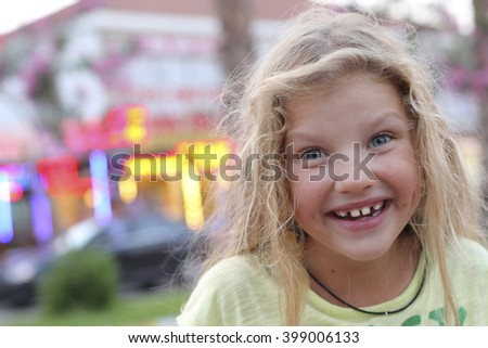 Seven years blonde surprised girl with big blue eyes open wide and white teeth looking at the camera, smiling wholeheartedly - stock photo