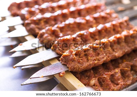 Several Adana Kebab skewers lined up waiting to be cooked and served - stock photo