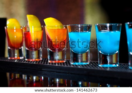Several alcoholic shots of different drinks at a party in a nightclub on the counter - stock photo