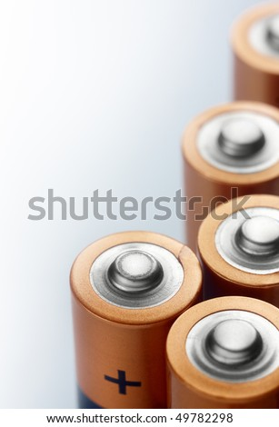Several alkaline batteries on a light colored background,closeup - stock photo