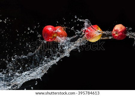 Several apple flying in space with the water on a black background - stock photo