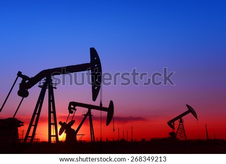 Several are operation of pumping unit under the setting sun, close-up  - stock photo
