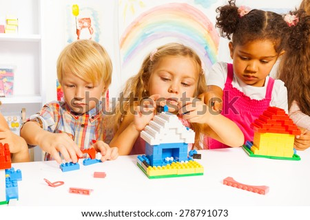 Several beautiful clever kids boys and girls playing with plastic blocks constructing houses in the kindergarten class - stock photo