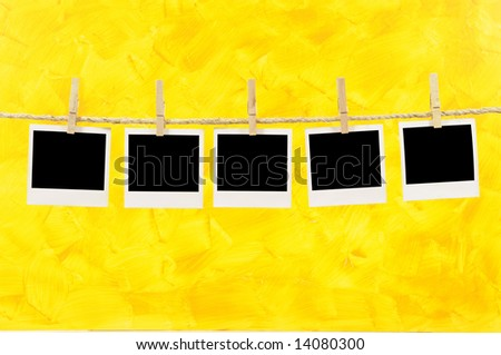 Several blank polaroid style instant camera photo prints hanging on a rope or string isolated against a painted yellow background.  Space for copy. - stock photo