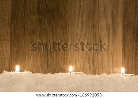 several candle in snow with wooden background - stock photo