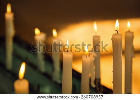 Several church candles against a dark background - stock photo