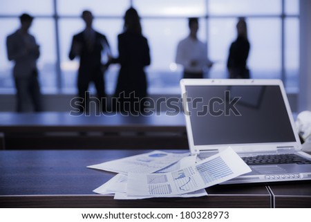 several colleagues communicating in office against window - stock photo