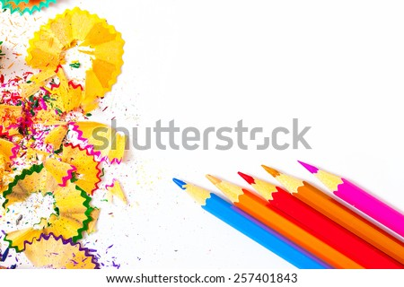 several colored pencils and shavings on white background with copy space, close up - stock photo