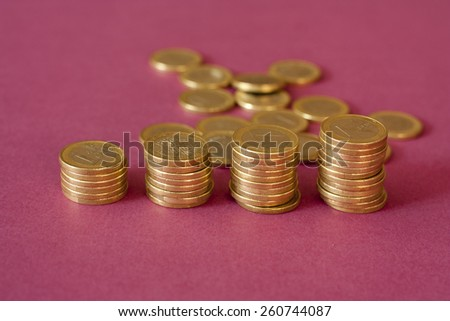 Several columns of coins on a purple background - stock photo
