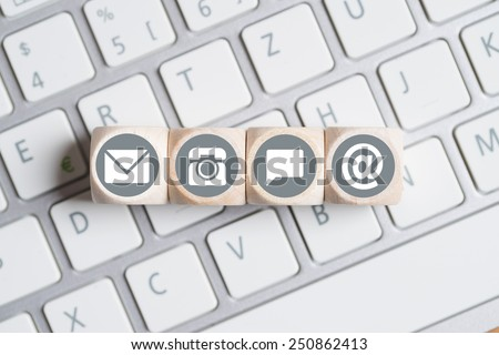 several contact options as icon on little cubes lying on a keyboard - stock photo