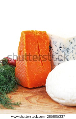 several  delicatessen types of cheese on wooden board with hot peppers and dill isolated on white background - stock photo
